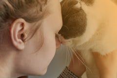 Das Mädchen umarmt ihre Katze, die Nahaufnahme, getont, das Thema der Freundschaft mit Haustieren stockfoto