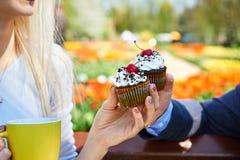 Das Mädchen und der Kerl in den Händen der Zeit nach einem kleinen Kuchen Stockfoto