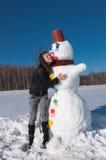 Das Mädchen und der Schneemann Lizenzfreies Stockbild