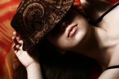 Das Mädchen und ein Hut. Lizenzfreie Stockbilder