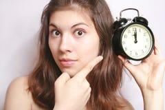 Das Mädchen und eine Alarmuhr. Lizenzfreies Stockfoto
