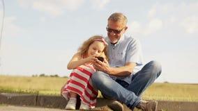 Das Mädchen und ihr reifer Vater spielen mit dem Smartphone und sitzen nicht durch die Seite der Straße stock footage