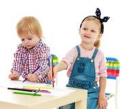 Das Mädchen und Junge, die am Tisch sitzen, zeichnen Stockfoto