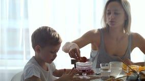 Das Mädchen und netter Junge, die Frühstück essen, essen Toast und Pfannkuchen stock video footage