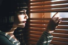 Das Mädchen untersucht die Schlitzfensterläden lizenzfreie stockfotografie