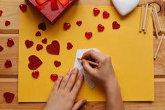 Das Mädchen unterzeichnet einen Umschlag mit Glückwünschen am Feiertag, um ihn, dazu auf den Holzoberflächelügengeschenken zu sen Stockfoto