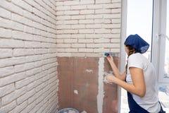 Das Mädchen vergipst manuell Nachahmung von Ziegelsteinen auf der Wand lizenzfreies stockbild