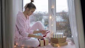 Das Mädchen verpackt ein Geschenk stock video