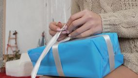 Das Mädchen verpackt einen Kasten mit einem Geschenk stock video