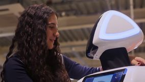 Das Mädchen verständigt sich mit dem Roboter und lächelt Moderne Robotertechnologien Künstliche Intelligenz kybernetisch stock footage
