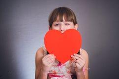 Das Mädchen versteckt sich hinter Herzen und blinzelt Stockfoto