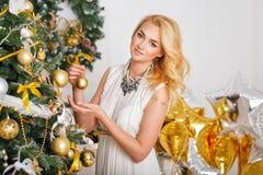 Das Mädchen verziert den Weihnachtsbaum Stockfoto