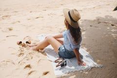 Das Mädchen von der Rückseite im Hut sitzt auf dem Strand Stockfotografie