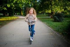 Das Mädchen von 7-8 Jahren reitet einen Roller im Stadtpark Lizenzfreies Stockbild