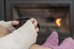Das Mädchen vor dem Kamin in den Wintersocken Lizenzfreie Stockfotos