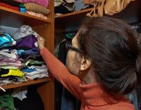 Das Mädchen wählt Kleidung in der Garderobe lizenzfreies stockfoto