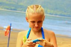 Das Mädchen wählte das Farbgerät in der Farbe des Badeanzugs Stockbild