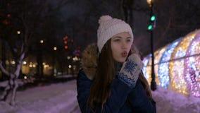 Das Mädchen wärmt ihre Hände mit ihrem Atem Im Winter ist es sehr kalt stock footage