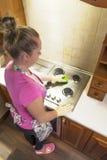 Das Mädchen wäscht den Ofen in der Küche Stockfoto