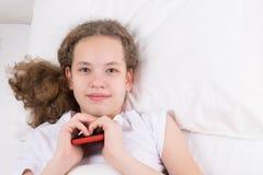 Das Mädchen wachte auf dem Bett auf und hält das Telefon in ihrer Hand Lizenzfreie Stockbilder