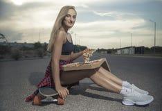 Das Mädchen, das weg von einem Skateboard mit headphonesGirl weder Skateboard oder longboard springt, liefert Pizza in der Stadt lizenzfreie stockfotos