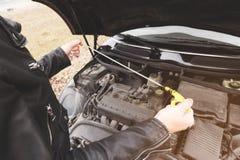 Das Mädchen, welches die Haube ihres Autos öffnet, überprüft den Maschinenölstand Lizenzfreie Stockfotos