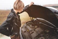 Das Mädchen, welches die Haube ihres Autos öffnet, überprüft den Maschinenölstand Stockfoto