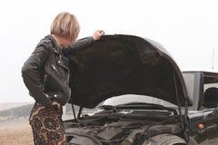 Das Mädchen, welches die Haube ihres Autos öffnet, überprüft den Maschinenölstand Lizenzfreies Stockbild