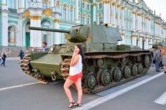 Das Mädchen wird auf dem Hintergrund des sowjetischen schweren Panzers fotografiert Lizenzfreies Stockbild