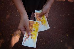 Das Mädchen wird durch das neue israelische Geld berechnet Stockbilder
