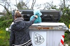 Das Mädchen wirft die Tasche mit dem Plastik in einen Abfallbehälter lizenzfreies stockfoto