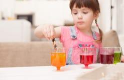 Das Mädchen wirft Farbe in der Schale für färbende Eier Lizenzfreies Stockfoto
