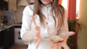 Das Mädchen wirft Kuchen vom Teig in Hände, klatscht ihre Hände und pulverisiert Mehl mit Fliegen Konzept: Produktion von Bonbons stock footage