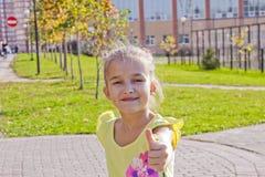 Das Mädchen wundert sich auf Kamille im Park Stockfoto