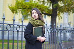 Das Mädchen am Zaun mit einem Buch Stockbild