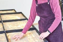Das Mädchen zeichnet auf den Sand mit ihren Händen stockbilder