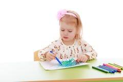 Das Mädchen zeichnet auf ein Blatt Papier Stockbilder