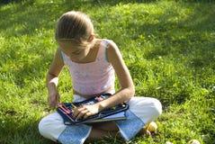 Das Mädchen zeichnet auf eine Wiese IV Stockfoto