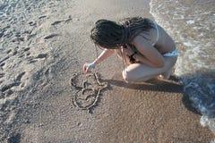 Das Mädchen zeichnet auf Sand Stockbilder