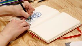 Das Mädchen zeichnet Bleistiftskizze auf Papier Abschluss oben Stockbilder