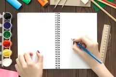 Das Mädchen zeichnet einen Bleistift in einem Notizbuch stockbild