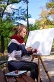 Das Mädchen zeichnet rote Farben auf dem Gestell Stockfoto