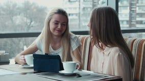 Das Mädchen zeigt der Freundin etwas auf der Berührungsfläche stock video footage