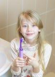Das Mädchen zeigt die Freuden einer elektrischen Zahnbürste Stockbild