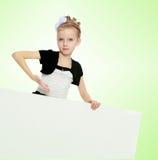 Das Mädchen zeigt eine Anzeigenfahne mit einem Finger Lizenzfreies Stockfoto