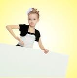 Das Mädchen zeigt eine Anzeigenfahne mit einem Finger Stockfoto