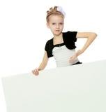Das Mädchen zeigt eine Anzeigenfahne mit einem Finger Lizenzfreies Stockbild