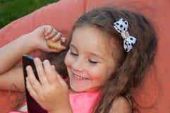 Das Mädchenkind mit dem Gerätmobile lacht Stockfoto