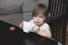 Das Mädchenkind mit einem Becher Stockfoto
