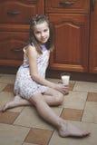 Das Mädchenkind mit einem Glas Milch Stockbild